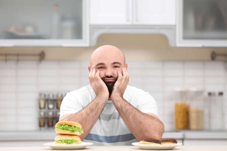 Overweight young man with unhealthy food at table in kitchen