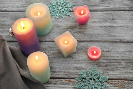 Wax candles burning on wooden table