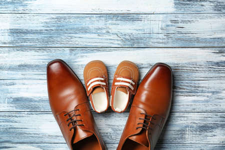 Big and small shoes on wooden background. Fathers day composition Stock Photo