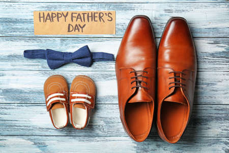 Bow tie, big and small shoes on wooden background. Father's day composition