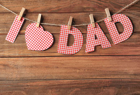 Text I LOVE DAD made of paper letters hanging on rope against wooden background Stock Photo