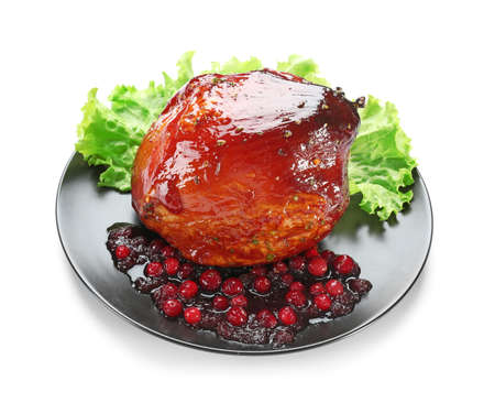 Plate with traditional honey baked ham and cranberry sauce, isolated on white