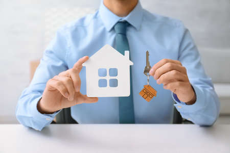 Real estate agent with key and house model at table