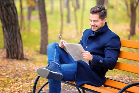 Young handsome man with newspaper sitting on bench in park