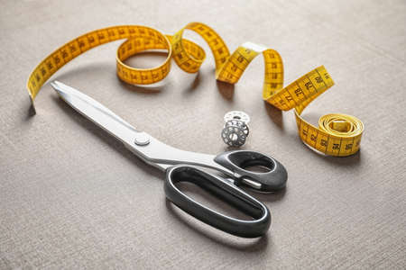 Measuring tape, bobbins and scissors for tailoring on fabric