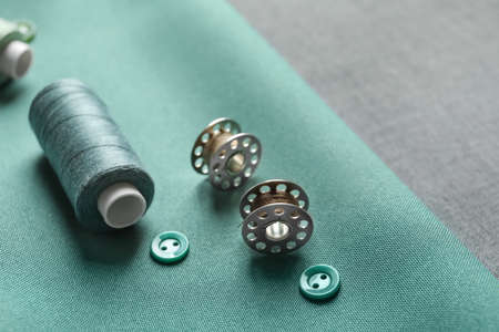 Threads, buttons and spools on fabric, closeup