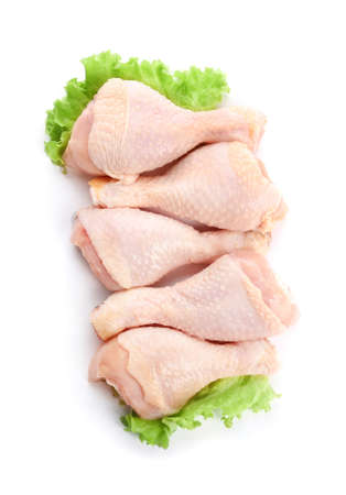 Raw chicken legs with lettuce on white background