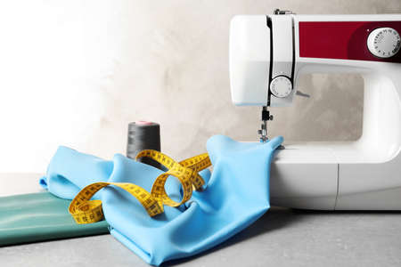 Sewing machine, fabric and measuring tape on table Stock Photo