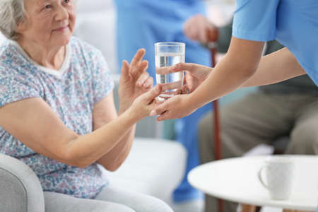 Young caregiver giving glass of water to senior woman indoors