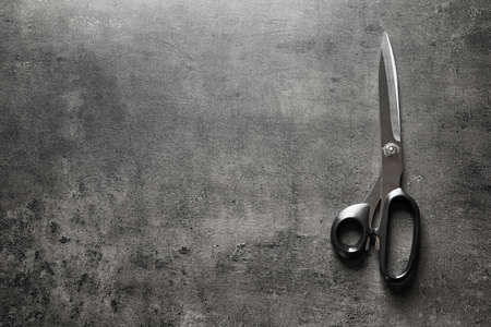 Tailoring scissors on grey background, top view