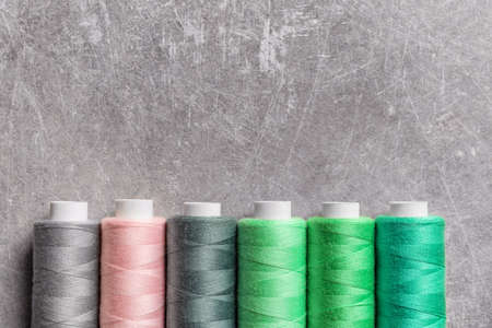 Multicolored threads on grey background Stock Photo