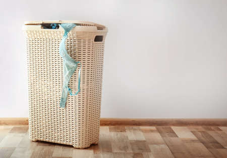 Bin with dirty underwear prepared for laundry indoors
