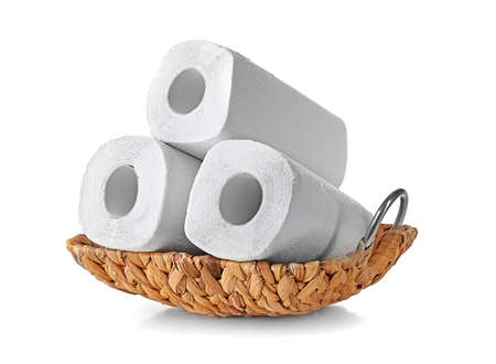 Wicker basket with rolls of paper towels on white background