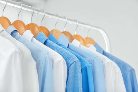 Hangers with clean shirts in laundry, closeup