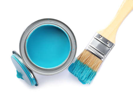 Can of blue paint and brush on white background, top view