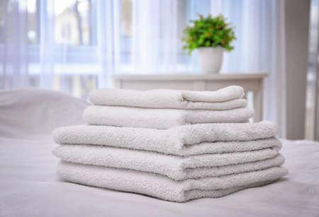 Białe ręczniki kąpielowe na łóżku w apartamencie hotelowym