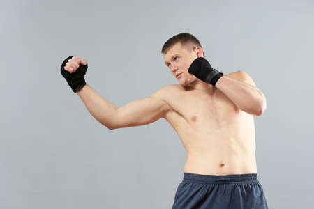 Attractive young boxer on grey background