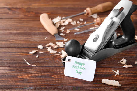 Card with text Happy Fathers Day and bench plane on wooden table