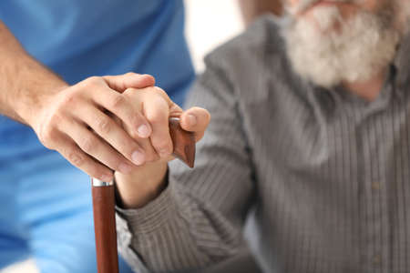 Senior man and young caregiver holding hands on walking stick, closeup