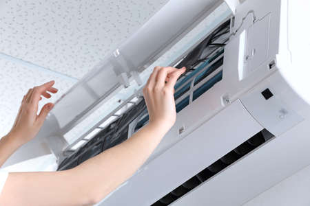 Young woman cleaning air conditioner, indoors