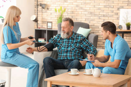 Senior man and young caregivers at home