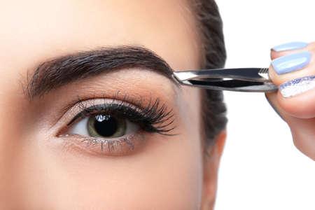 Mujer joven corregir la forma de las cejas, primer plano