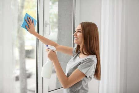 Schöne Frau, die Fenster zu Hause putzt