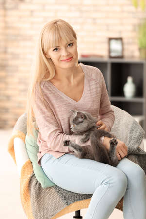 Young woman holding cute cat at home