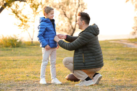 Father zipping up jacket of little son outdoors