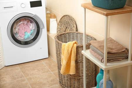 Wicker basket with laundry near washing machine in bathroom Stock Photo