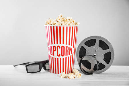 Tasty popcorn, glasses and movie reel on table against light background