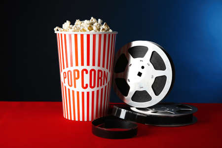 Paper cup with tasty popcorn and movie reel on table against dark background