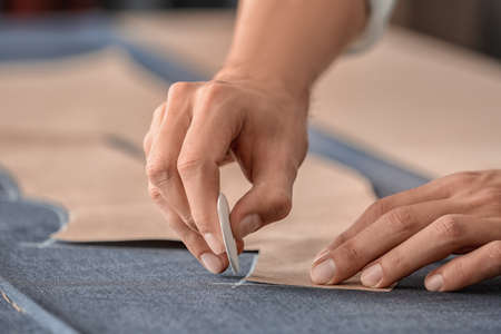 Young tailor working with sewing pattern, closeup