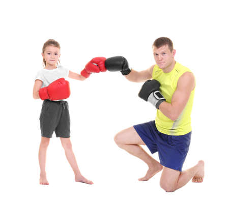 Cute little girl training with boxing coach on white background Stock Photo