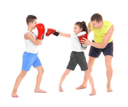 Cute little children training with boxing coach on white background