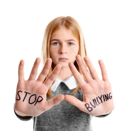 Teenage girl with words Stop bullying on her hands against white background Stock Photo