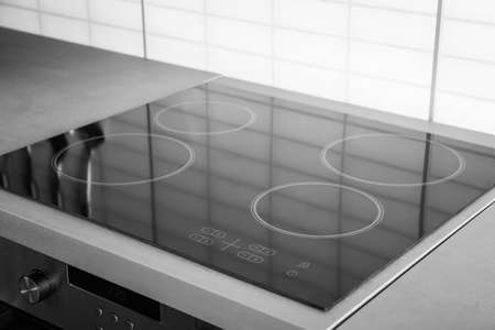 New electric stove with induction cooktop in kitchen, closeup Archivio Fotografico