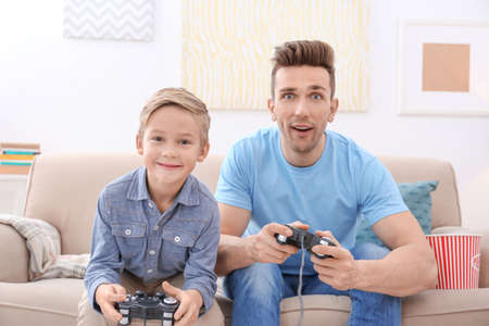 Cute boy and his father playing videogame at home