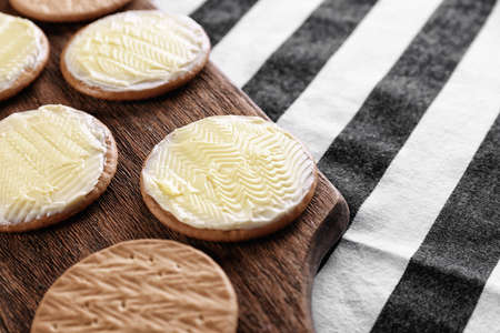 Tasty cookies with butter on wooden board, closeup Stock Photo
