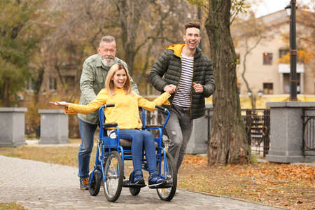 Happy woman in wheelchair with her family outdoors on autumn day Stockfoto