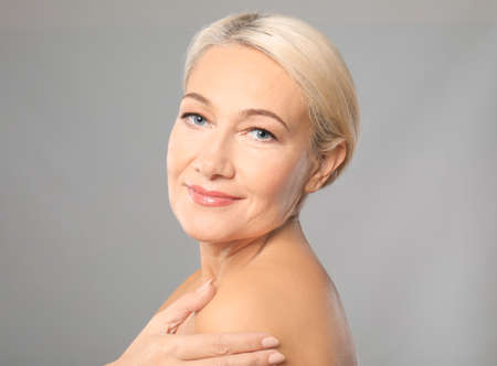Portrait of beautiful mature woman on grey background. Skin care concept Stock Photo