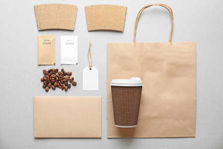 Composition with blank cup, paper bag and sugar packages as mockups for branding on grey background