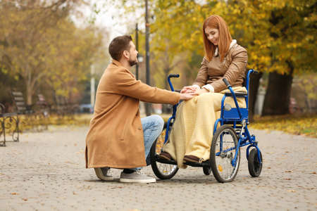 Young woman in wheelchair and her husband outdoors on autumn day Stock Photo