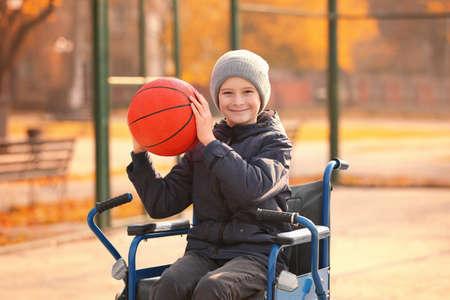 Petit garçon en fauteuil roulant avec ballon sur aire de jeux Banque d'images