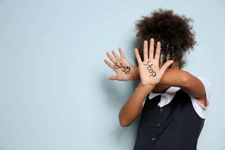 Little African-American girl with phrase Stop bullying on light background