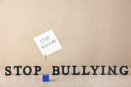 Note with text Stop bullying on pad holder against light background