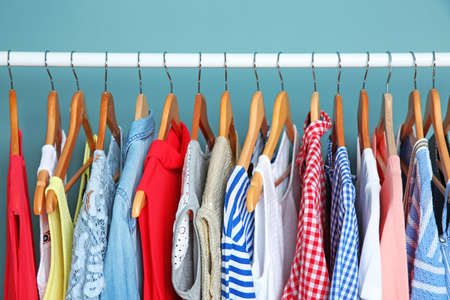 Rack with different clothes near color wall Stockfoto