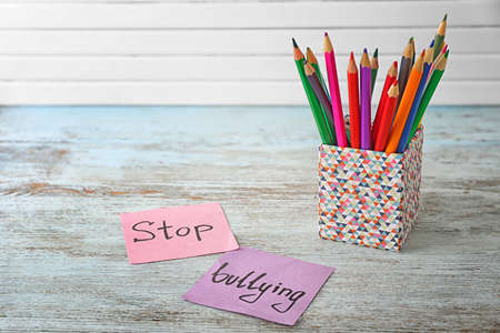 Notes with text Stop bullying and pencil holder on table Stock Photo