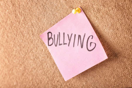 Note with word Bullying pinned to board