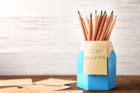 Sticky note with text Stop bullying on pencil holder